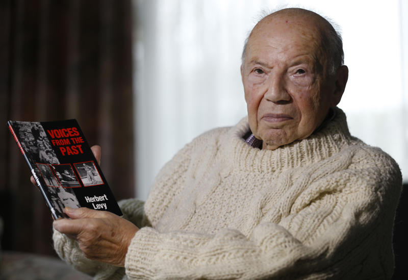 """In this Thursday, Nov. 21, 2013 photo, shows Herbert Levy, 84, who was brought to England by Kindertransport from Berlin in Germany in 1939 to escape Nazi persecution, holds a copy of his book """"Voices from the Past"""" at his home in London. The operation was called Kindertransport - Children's Transport - and it was a passage from hell to freedom. Kristallnacht had just rocked Nazi Germany. The pogroms killed dozens of Jews, burned hundreds of synagogues and imprisoned tens of thousands in concentration camps. Many historians see them as the start of Hitler's Final Solution. (AP Photo/Kirsty Wigglesworth)"""