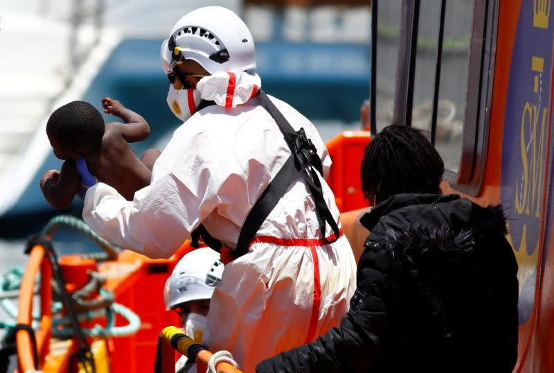 Rescuers help a migrant child to disembark from a Spanish coast guard vessel, in the port of Arguineguin