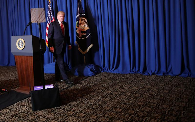 Donald Trump looks serious as he walks away from a presidential press conference podium in Mar-a-Lago - Credit: Carlos Barria/Reuters