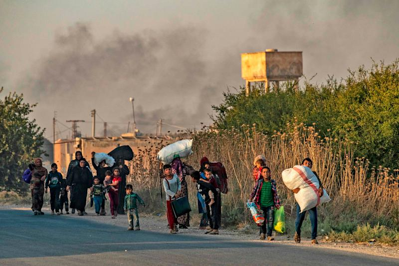 Civilians flee with their belongings amid Turkish bombardment on Syria's northeastern town of Ras al-Ain in the Hasakeh province along the Turkish border on Oct. 9, 2019. Turkey launched a broad assault on Kurdish-controlled areas in northeastern Syria, with intensive bombardment paving the way for an invasion made possible by the withdrawal of US troops.