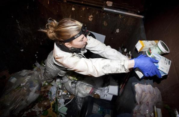 Anna-Rae Douglass, 23, a practicing 'freegan,' sorts through a dumpster for edible food behind an organic grocery store in Coquitlam, British Columbia April 5, 2012.