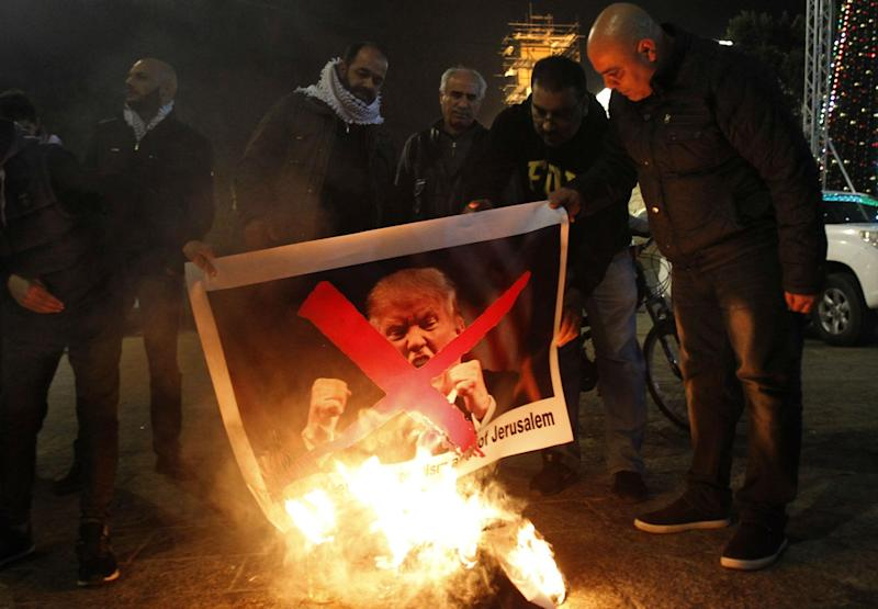 Palestinian protesters burn pictures of US President Donald Trump at the manger square in Bethlehem on December 5, 2017 (MUSA AL SHAER/AFP/Getty Images)