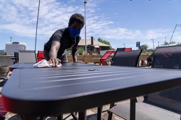 An Ottawa restaurant worker cleans a patio table on Thursday in advance of today's reopening, which will allow people once again eat outside at bars and restaurants. (Francis Ferland/CBC - image credit)