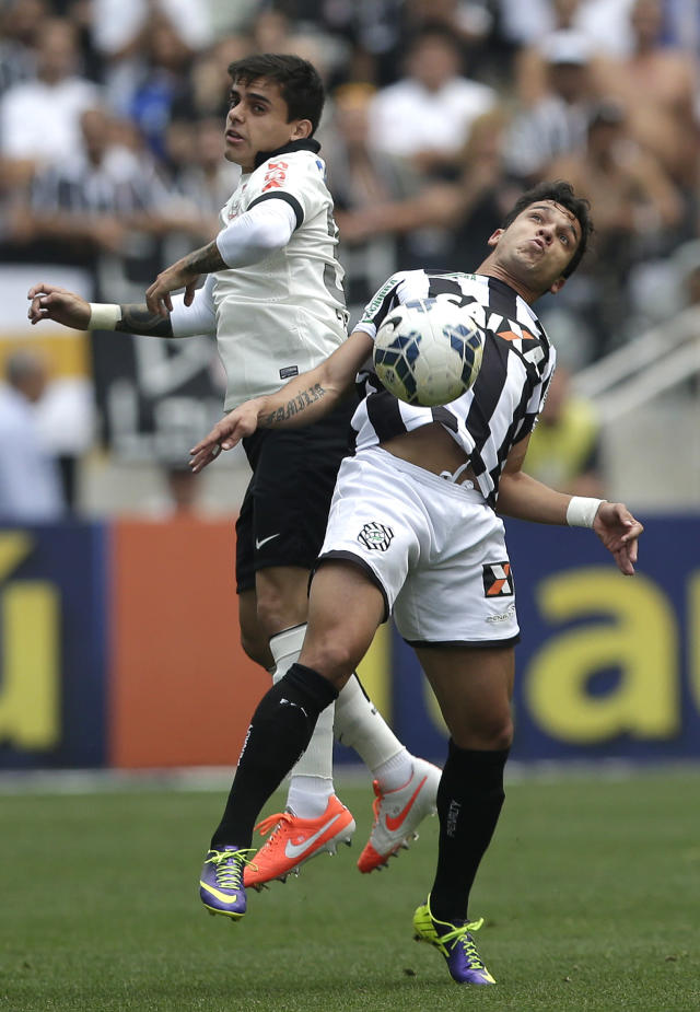 Corinthians's Fagner, left, fights for a ball with Figueirense's Everton Santos, during a Brazilian soccer league match at the Itaquerao, the still unfinished stadium, in Sao Paulo, Brazil, Sunday, May 18, 2014. Only 40,000 tickets were put on sale for Corinthians' match against Figueirense because some of the 20,000 temporary seats needed for the World Cup opener are still being installed. The stadium will host the World Cup opener match between Brazil and Croatia on June 12. (AP Photo/Andre Penner)