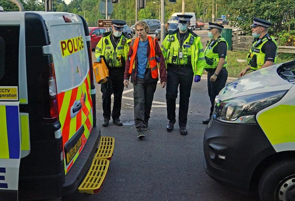 Officers lead a protester to a police van at a slip road at Junction 18 of the M25 (Steve Parsons/PA) (PA Wire)