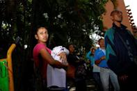 A woman carrying a baby queues as she trys to buy food outside a supermarket in Caracas, Venezuela March 10, 2017. REUTERS/Carlos Garcia Rawlins