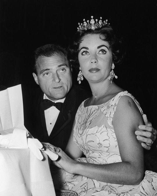 <p>Taylor, known for her amazing jewelry and multiple husbands, wore a dainty floral print dress with full skirt when she attended the Golden Globes in 1957. She accessorized the look with a tiara, chandelier earrings, and Mike Todd (aka hubby No. 3). (Photo: Getty Images) </p>