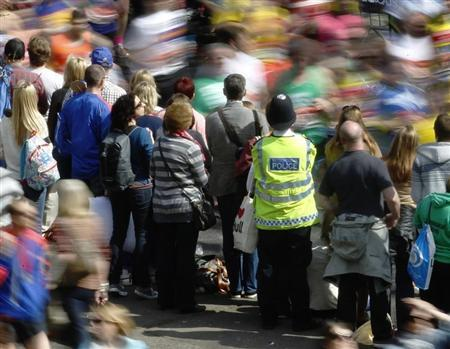 A policeman observes runners and crowd during the London Marathon