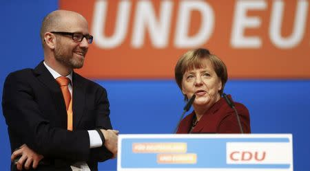 Germany's Christian Democratic Union (CDU) secretary general Peter Tauber stands on stage with Chancellor Angela Merkel as they tour the venue in Karlsruhe, December 13, 2015, where CDU will hold a two-day congress on Monday.   REUTERS/Kai Pfaffenbach