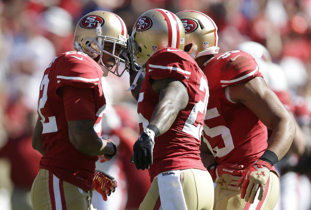 San Francisco 49ers cornerback Carlos Rogers, left, celebrates after intercepting Arizona Cardinals quarterback Carson Palmer's pass with cornerback Tarell Brown, center, and safety Eric Reid during the first quarter of an NFL football game in San Francisco, Sunday, Oct. 13, 2013. (AP Photo/Marcio Jose Sanchez)