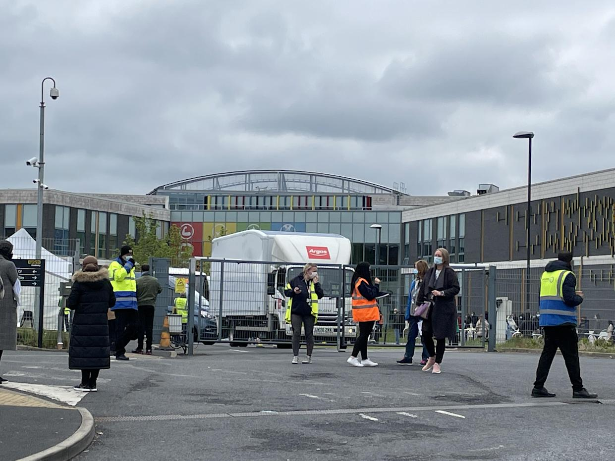 People queue for the vaccination centre at the Essa Academy in Bolton. The Indian coronavirus variant has been detected in a number of areas in England, including Bolton, which are reporting the highest rates of infection, data suggests. Picture date: Friday May 14, 2021.