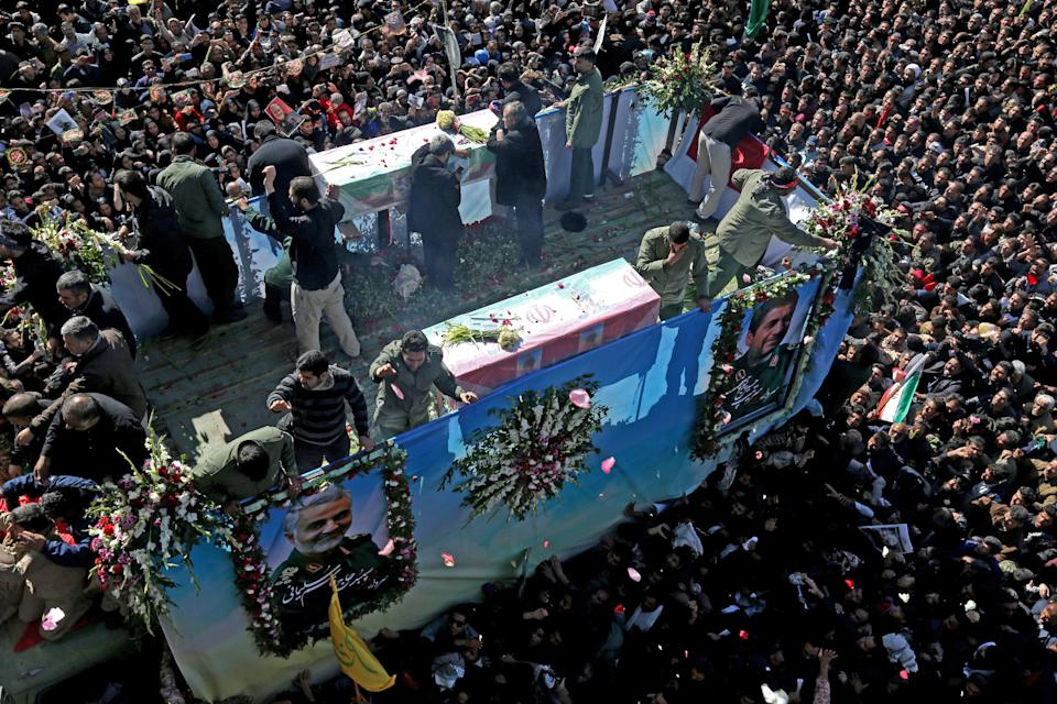 """Iranian mourners gather around a vehicle carrying the coffin of slain top general Qasem Soleimani during the final stage of funeral processions, in his hometown Kerman on January 7, 2020. - Soleimani was killed outside Baghdad airport Friday in a drone strike ordered by US President Donald Trump, ratcheting up tensions with arch-enemy Iran which has vowed """"severe revenge"""". The assassination of the 62-year-old heightened international concern about a new war in the volatile, oil-rich Middle East and rattled financial markets. (Photo by ATTA KENARE / AFP) (Photo by ATTA KENARE/AFP via Getty Images)"""