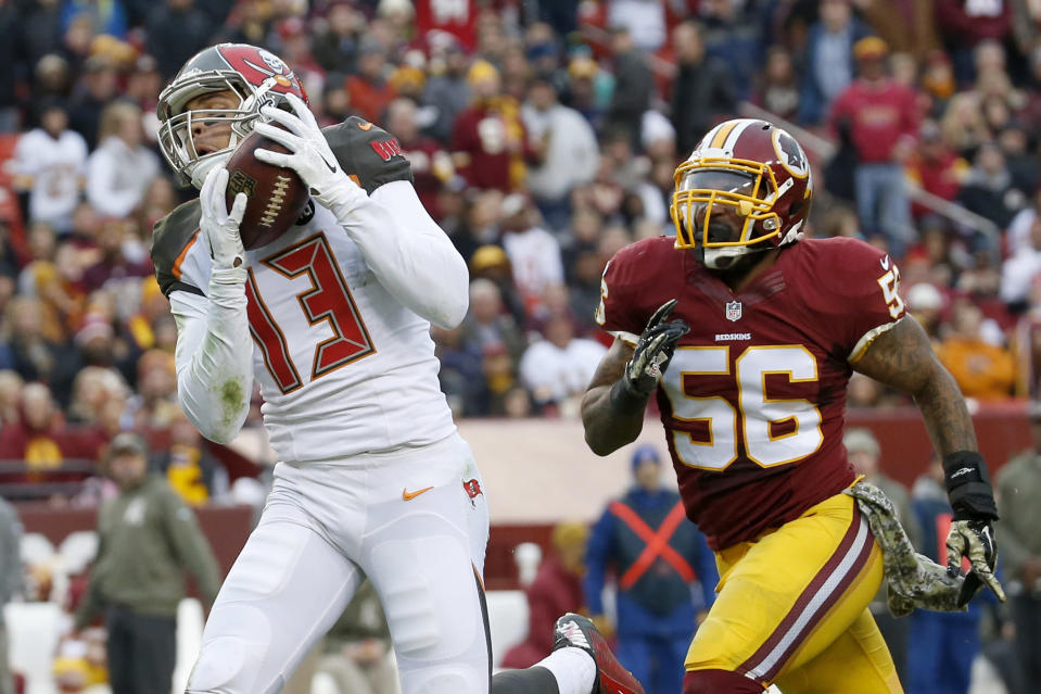 Tampa Bay Buccaneers wide receiver Mike Evans (13) pulls in a touchdown pass as Washington Redskins inside linebacker Perry Riley (56) pursues during the second half of an NFL football game in Landover, Md., Sunday, Nov. 16, 2014. (AP Photo/Alex Brandon)