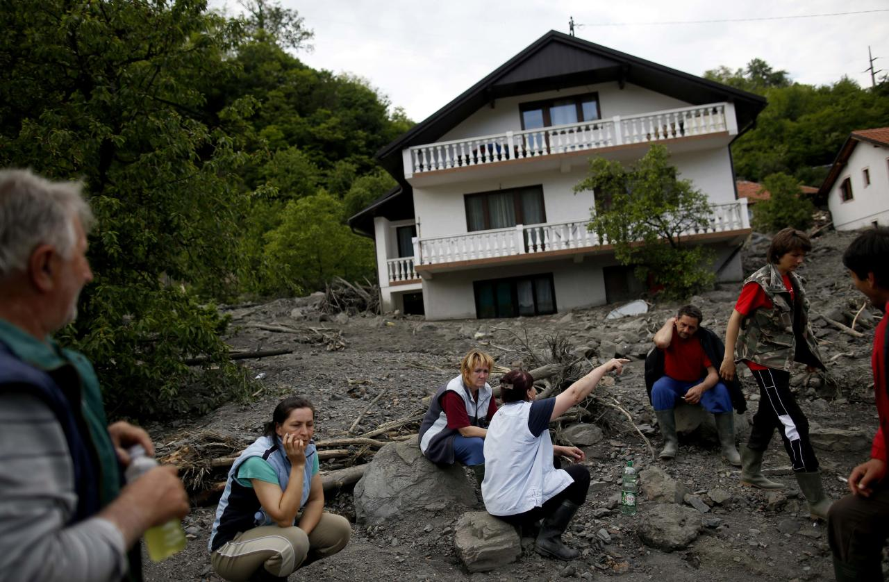 The Kovacevic family sits in front of their flood-damaged house in Topcic Polje, May 20, 2014. At least 40 people have died in Serbia, Bosnia and Croatia, after days of the heaviest rainfall since records began 120 years ago caused rivers to burst their banks and triggered hundreds of landslides. REUTERS/Dado Ruvic (BOSNIA AND HERZEGOVINA - Tags: DISASTER ENVIRONMENT)