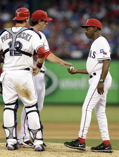 Texas Rangers manager Ron Washington, right, pulls starting pitcher Derek Holland from the game as catcher A.J. Pierzynski (12) watches during the fifth inning of a baseball game against the Cleveland Indians Tuesday, June 11, 2013, in Arlington, Texas. (AP Photo/LM Otero)