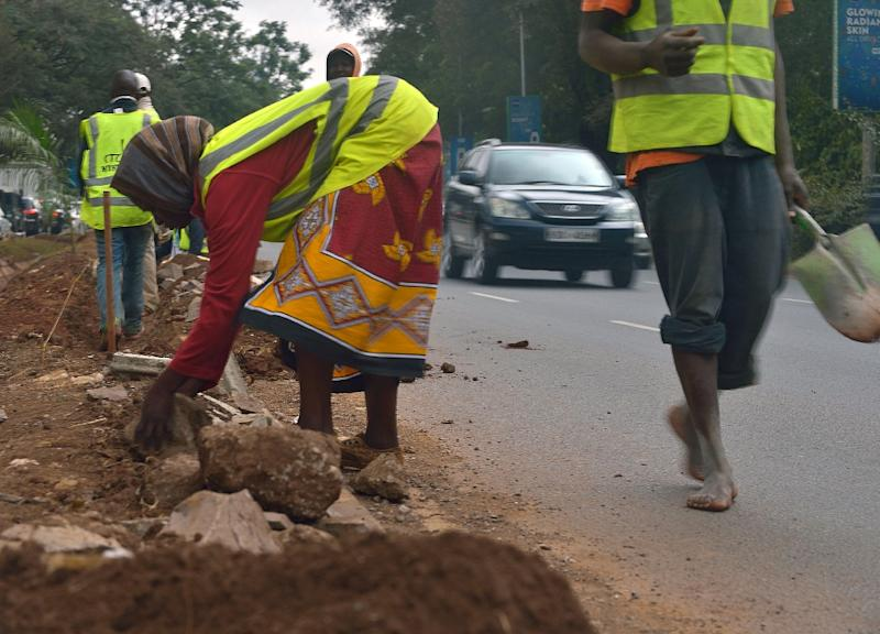 Workers repave a kerb along a street in Nairobi on July 9, 2015 (AFP Photo/Tony Karumba)