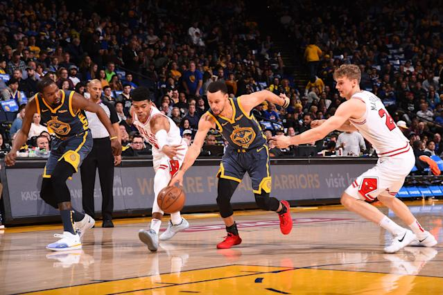 OAKLAND, CA - JANUARY 11: Chandler Hutchison #15 of the Chicago Bulls and Stephen Curry #30 of the Golden State Warriors reach for control of a loose ball on January 11, 2019 at ORACLE Arena in Oakland, California. (Photo by Noah Graham/NBAE via Getty Images)