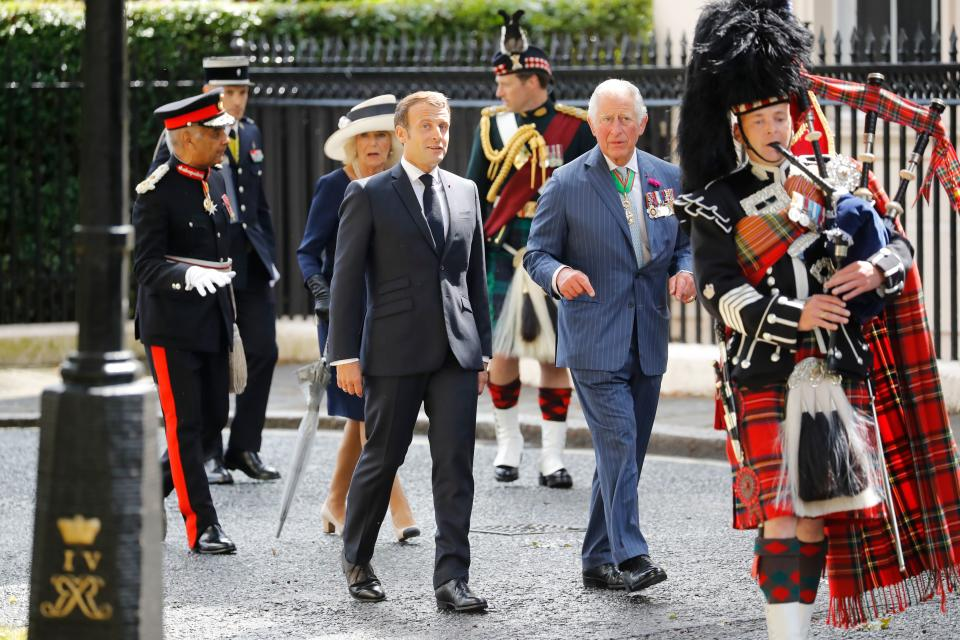 Camilla, Charles and Macron follow a piper as they arrive to lay wreaths at the statue of former French president Charles de Gaulle at Carlton Gardens. (Getty Images)