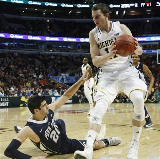 Penn State's Nick Colella (20) falls as he defends Michigan's Nik Stauskas (11) during the second half of an NCAA college basketball game at the Big Ten tournament Thursday, March 14, 2013, in Chicago. (AP Photo/Charles Rex Arbogast)