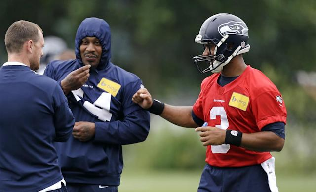Seattle Seahawks quarterback Russell Wilson, right, greets running back Marshawn Lynch at a football minicamp practice Tuesday, June 17, 2014, in Renton, Wash. (AP Photo/Elaine Thompson)