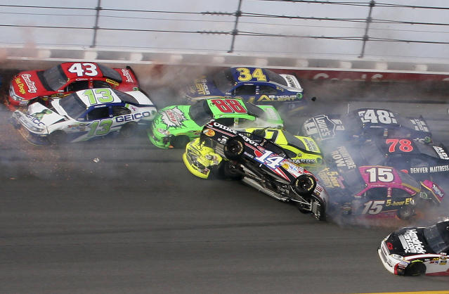 Tony Stewart (14) flips over as Clint Bowyer (15), Regan Smith (78), Jeff Burton (31), Jimmie Johnson (48), Casey Mears (13), Aric Almirola (43), Dale Earnhardt Jr. (88) and David Ragan (34) crash around him during the NASCAR Sprint Cup Series auto race at Talladega Superspeedway in Talladega, Ala., Sunday, Oct. 7, 2012. (AP Photo/Dale Davis)
