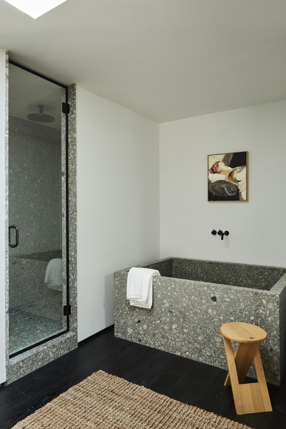 An oil painting by Robert Malherbe from BDDW adorns the wall above the custom tub by OSKLO in extra honed ceppo di gre stone from Stoneland, with Vola tub fittings from EuroConcepts. The Roger Tallon folding stool is from 1stdibs.