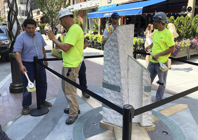 Sculptor Pablo Eduardo, left, and workers make final touches to stone pillars stand along Boylston Street after installation was finished, Monday, Aug. 19, 2019, in Boston to memorialize the Boston Marathon bombing victims at the sites where they were killed. Martin Richard, Krystle Campbell and Lingzi Lu were killed when bombs were detonated at two locations near the finish line on April 15, 2013. (AP Photo/Philip Marcelo)