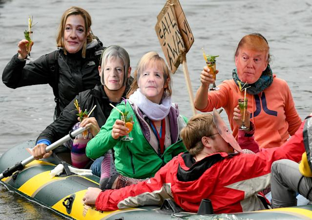 <p>Participants of the protest against the G20 Summit demonstrate on an inflatable boat wearing masks with the likeness of from left: High Representative of the European Union for Foreign Affairs, Federica Mogherini, British Prime Minister Theresa May, German Chancellor Angela Merkel and US President Donald Trump in Hamburg, Germany, Sunday, July 2, 2017. (Axel Heimken/dpa via AP) </p>