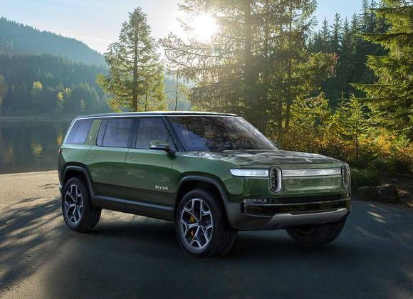 The Rivian R1S, a boxy green SUV with a futuristic front end, in a wooded setting.
