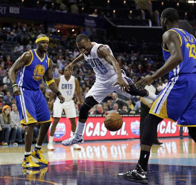 Charlotte Bobcats' Kemba Walker (15) is fouled as he drives between Golden State Warriors' Jermaine O'Neal (7) and Draymond Green during the first half of an NBA basketball game in Charlotte, N.C., Monday, Dec. 9, 2013. (AP Photo/Chuck Burton)