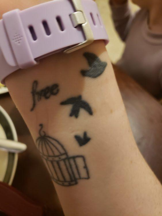 Angelica shows the viewer a tattoo of three birds that are flying out of the cage. They are supposed to represent the same bird flying more and more steadily as it gets farther away from the cage. The word 'free' is written in cursive.