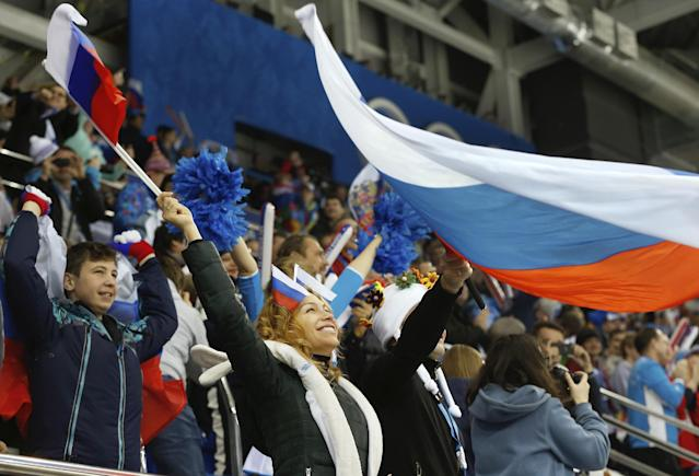 A Russian fan celebrates a goal during the third period of the game against Germany at the 2014 Winter Olympics women's ice hockey game at Shayba Arena, Sunday, Feb. 9, 2014, in Sochi, Russia. (AP Photo/Petr David Josek)