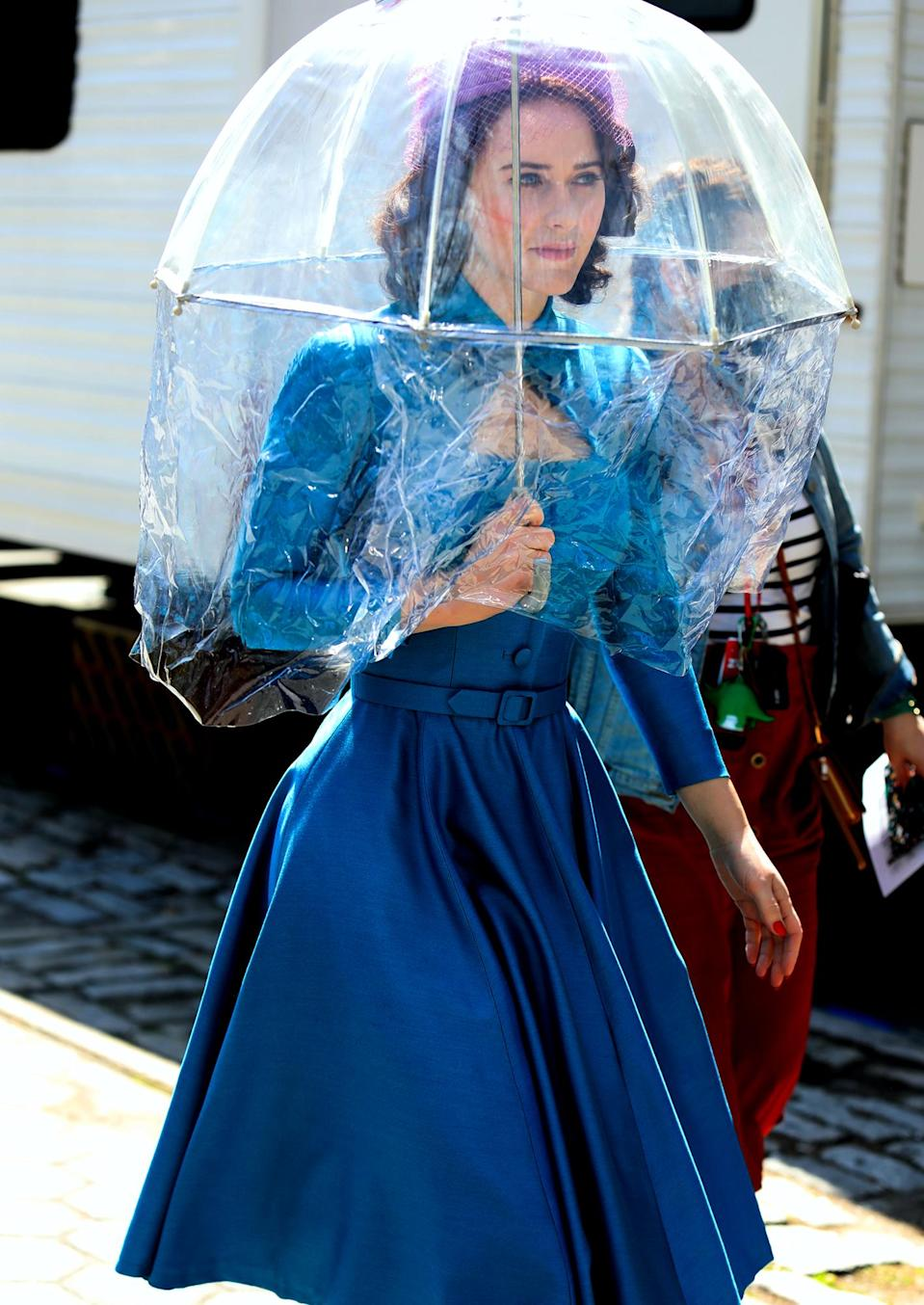 <p>Rachel Brosnahan heads to<em> The Marvelous Mrs. Maisel</em> set underneath an umbrella on Thursday in N.Y.C.</p>