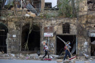 Women with brooms pass by a historic building damaged by Tuesday's explosion in the Gemmayzeh neighborhood, Beirut, Lebanon, Saturday, Aug. 8, 2020. Senior officials from the Middle East and Europe started arriving in Lebanon Saturday in a show of solidarity with the tiny country that suffered a deadly blast this week which caused large-scale damage to the capital Beirut. (AP Photo/Hassan Ammar)