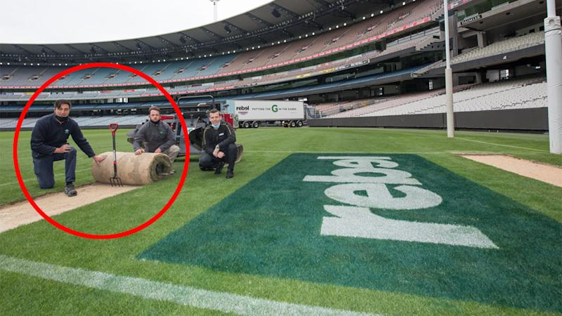 MCG curators can be seen here rolling up part of the turf to be transported to Brisbane.