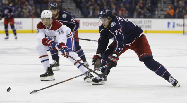 Montreal Canadiens' Jesperi Kotkaniemi, left, of Finland, tries to knock the puck away from Columbus Blue Jackets' Josh Anderson during the second period of an NHL hockey game Thursday, March 28, 2019, in Columbus, Ohio. (AP Photo/Jay LaPrete)