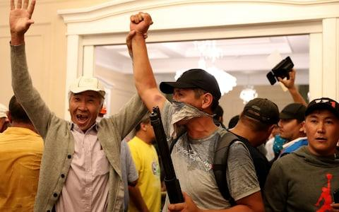 Supporters of the former president celebrate in his private residence after fending off the attack - Credit: IGOR KOVALENKO/EPA