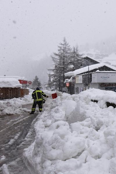 Workers worked to clear the snow as thousands of tourists were stranded in Zermatt