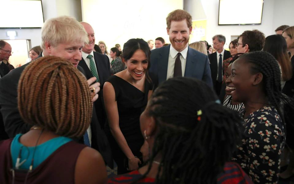 Boris Johnson, Meghan and Prince Harry in happier times - AFP