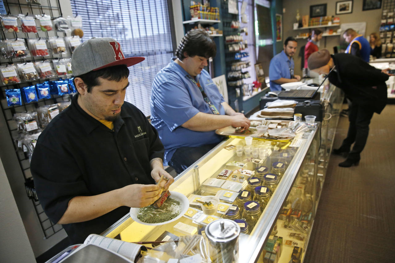 Employees roll joints behind the sales counter at Medicine Man marijuana dispensary, which is to open as a recreational outlet at the start of 2014, in Denver, Friday Dec. 27, 2013. Medicine Man was among the first batch of Denver businesses which received their licenses allowing them to legally sell recreational marijuana on Friday. (AP Photo/Brennan Linsley)