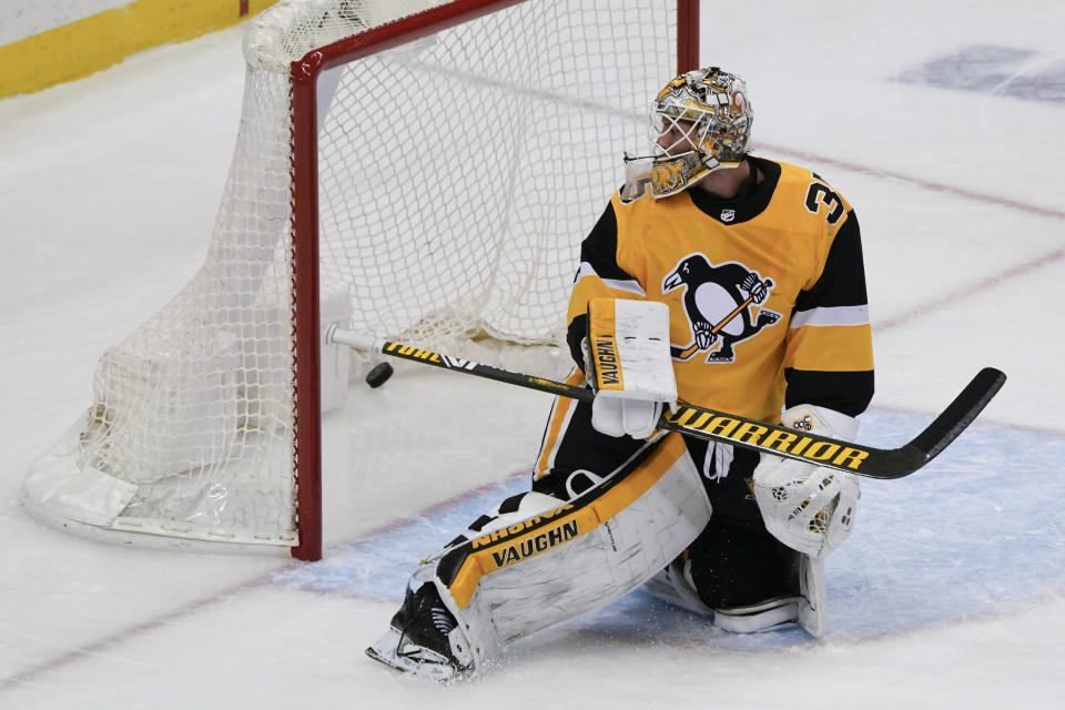 Pittsburgh Penguins goaltender Tristan Jarry looks behind him at the puck on a goal scored by Philadelphia Flyers' Scott Laughton that tied the score during the third period of an NHL hockey game Thursday, March 4, 2021, in Pittsburgh. (AP Photo/Keith Srakocic)
