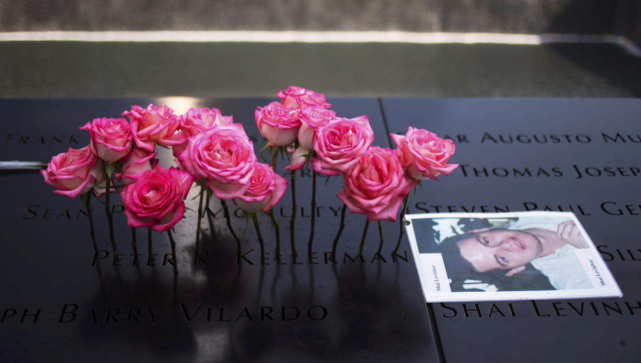 Roses are placed on the inscribed name of Peter Kellerman next to an image of Shai Levinhar along the North Pool during 9/11 Memorial ceremonies marking the 12th anniversary of the 9/11 attacks on the World Trade Center in New York on September 11, 2013. REUTERS/Adrees Latif (UNITED STATES - Tags: DISASTER ANNIVERSARY)