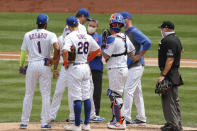 A trainer visits New York Mets starting pitcher Jacob deGrom, third from left, on the mound during the first inning of a baseball game against the Miami Marlins at Citi Field, Sunday, Aug. 9, 2020, in New York. (AP Photo/Kathy Willens)