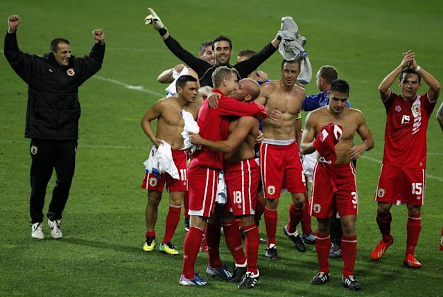 Gibraltar's players celebrate at the end of a friendly soccer match between Gibraltar and Slovakia at the Algarve stadium in Faro, southern Portugal, Tuesday, Nov. 19, 2013. Gibraltar played its first international soccer match as a new full member of the UEFA after they were accepted in May. The match ended in a 0-0 draw. (AP Photo/Francisco Seco)