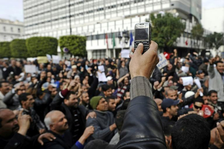 A protester records with his mobile phone a demonstration in central Tunis on January 19, 2011
