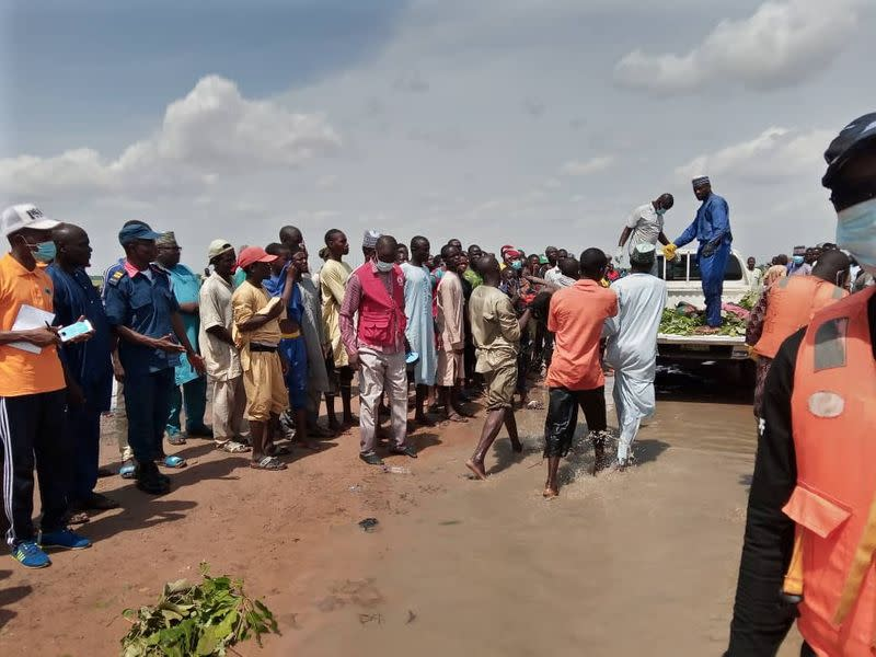 People are seen gathered around a truck as a boy, one of the victim of a boat accident, is being carried to a truck in Kebbi