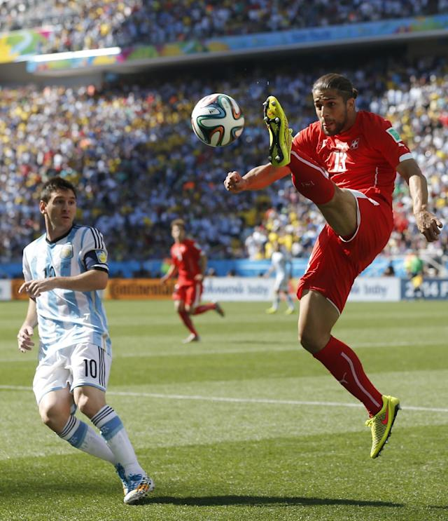 Switzerland's Ricardo Rodriguez, right, clears the ball from Argentina's Lionel Messi during the World Cup round of 16 soccer match between Argentina and Switzerland at the Itaquerao Stadium in Sao Paulo, Brazil, Tuesday, July 1, 2014. (AP Photo/Frank Augstein)