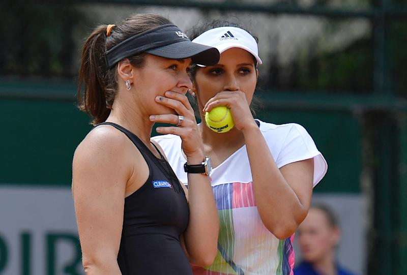 Switzerland's Martina Hingis speaks to India's Sania Mirza during their women's first round doubles match at the French Open in Paris