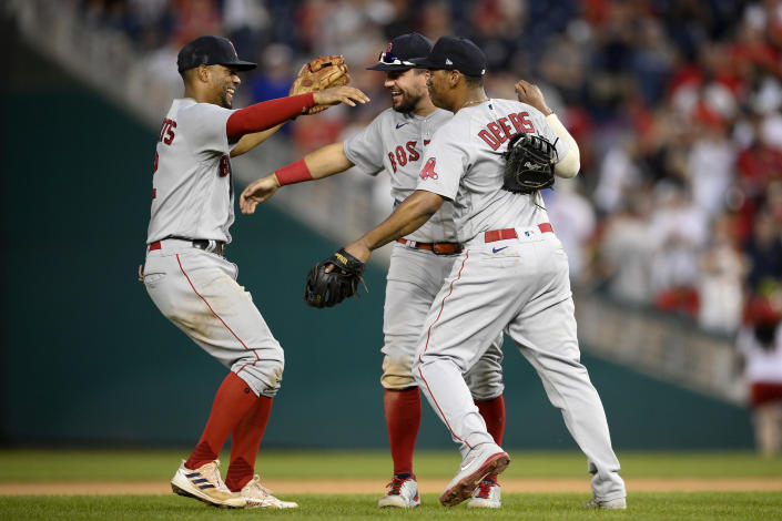 Boston Red Sox's Xander Bogaerts, left, Kyle Schwarber, center and Rafael Devers, right, celebrate after a baseball game against the Washington Nationals, Sunday, Oct. 3, 2021, in Washington. (AP Photo/Nick Wass)