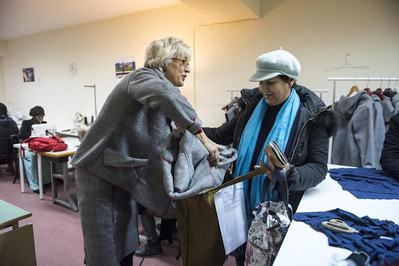 In this Monday, Jan. 30, 2017, project organizer Elke Wollschlagerr from Germany, left, gives a jacket made from a blanket to a Greek woman, at a tiny workshop charity called Naomi in the northern Greek city of Thessaloniki, which is working long hours to collect and wash discarded blankets and turn them into wearable coats. The blankets are mostly army issue gray with red stitching and are distributed as aid at the sprawling refugee and migrant encampments, and are being recycled into practical coats for the vulnerable refugees who are facing a harsh winter. (AP Photo/Giannis Papanikos)